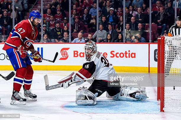 Goaltender Louis Domingue of the Arizona Coyotes allows a goal while Alexander Radulov of the Montreal Canadiens watches during the NHL game at the...