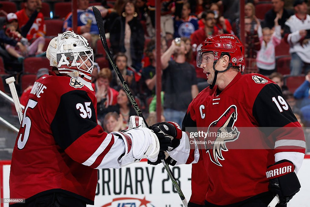 Goaltender Louis Domingue #35 of the Arizona Coyotes is congratulated by Shane Doan #19 after defeating the Calgary Flames 4-1 in the NHL game at Gila River Arena on February 12, 2016 in Glendale, Arizona.
