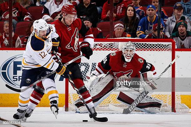Goaltender Louis Domingue of the Arizona Coyotes prepares to make a save as Brian Gionta of the Buffalo Sabres attempts a deflection past Martin...