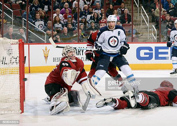 Goaltender Louis Domingue of the Arizona Coyotes reaches for the puck on a shot wide of the goal as Blake Wheeler of the Winnipeg Jets positions...