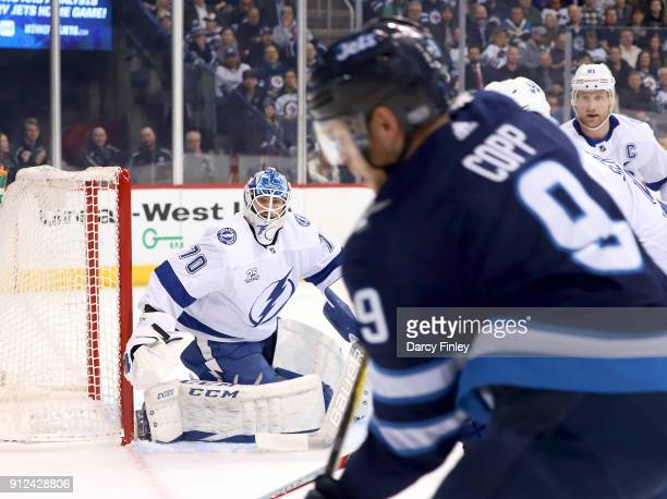 Goaltender Louis Domingue of the Tampa Bay Lightning keeps an eye on the play along the boards during first period action against the Winnipeg Jets...