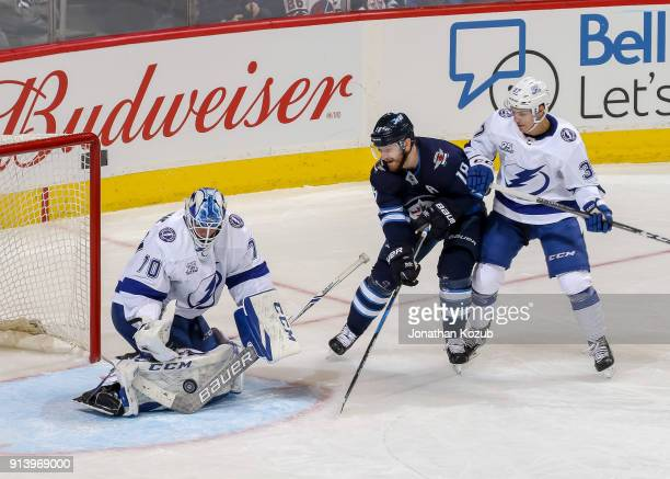 Goaltender Louis Domingue Yanni Gourde of the Tampa Bay Lightning and Bryan Little of the Winnipeg Jets track the puck as it flies in the crease...