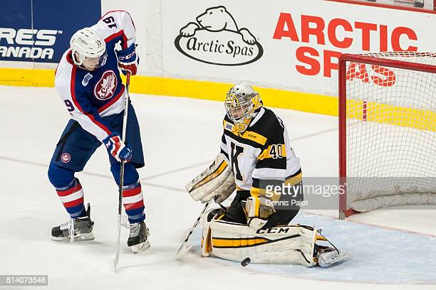 Goaltender Lucas Peressini of the Kingston Frontenacs makes a kick save on a deflection from forward Christian Fischer of the Windsor Spitfires on...