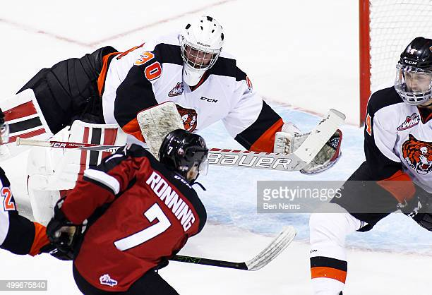 Goaltender Mack Shields of the Medicine Hat Tigers makes a save against Ty Ronning of the Vancouver Giants during the first period of their WHL game...