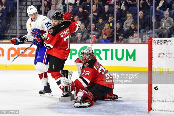 Goaltender Mackenzie Blackwood of the Binghamton Devils allows a goal in the second period while teammate Brian Strait defends against Michael...