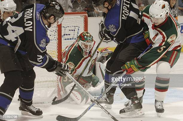 Goaltender Manny Fernandez of the Minnesota Wild makes a save on Anze Kopitar and Alexander Frolov of the Los Angeles Kings during the NHL game on...
