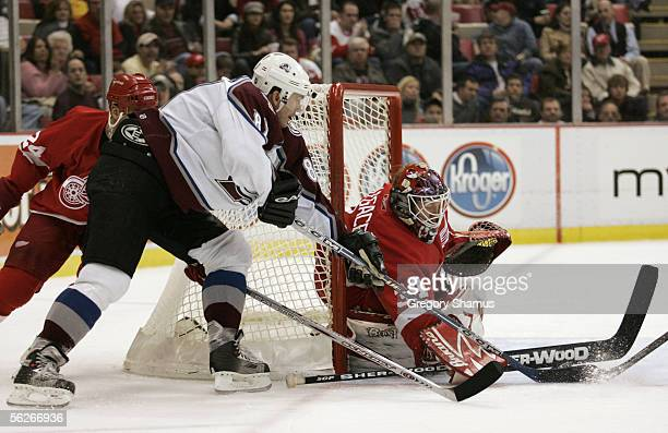 Goaltender Manny Legace of the Detroit Red Wings makes a save on Pierre Turgeon of the Colorado Avalanche during third period action on November 23...