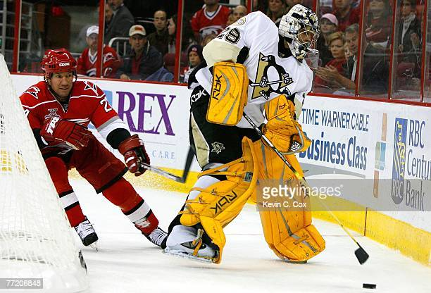 Goaltender Marc-Andre Fleury of the Pittsburgh Penguins clears the puck from an attacking Scott Walker of the Carolina Hurricanes during the second...