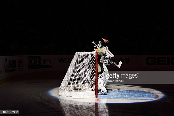 Goaltender MarcAndre Fleury of the Pittsburgh Penguins is bathed in a spotlight during the US National Anthem before a game against the Carolina...