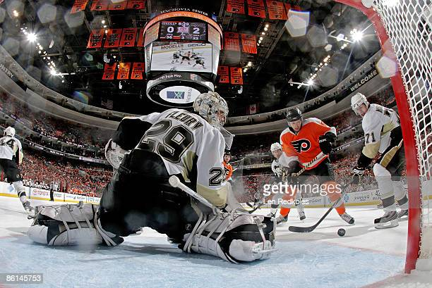 Goaltender MarcAndre Fleury of the Pittsburgh Penguins keeps his eye on the puck as teammate Evgeni Malkin battles with Joffrey Lupul of the...