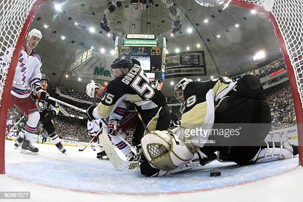 Goaltender MarcAndre Fleury of the Pittsburgh Penguins looks for the puck underneath him as Sergei Gonchar of the Penguins defends against Martin...