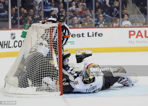 Goaltender MarcAndre Fleury teammate Colin Miller of the Vegas Golden Knights and Blake Wheeler of the Winnipeg Jets work to untangle themselves in...