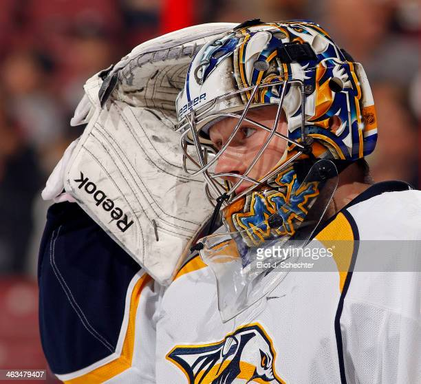 Goaltender Marek Mazanec of the Nashville Predators pulls his helmet on after a break in the action against the Florida Panthers at the BBT Center on...