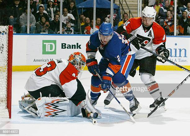 Goaltender Martin Biron of the Philadelphia Flyers makes a pad save as teammate Kimmo Timonen and Josh Bailey of the New York Islanders look for the...