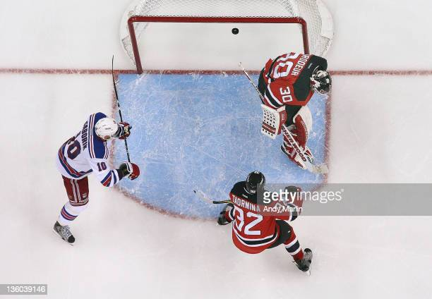 Goaltender Martin Brodeur and Matt Taormina of the New Jersey Devils look away as Marian Gaborik of the New York Rangers scores the winning goal...