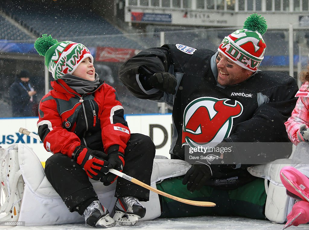 Goaltender Martin Brodeur #30 of the New Jersey Devils and son Maxime sit on the ice during the 2014 NHL Stadium Series family skate at Yankee Stadium on January 25, 2014 in the Bronx borough of New York City.