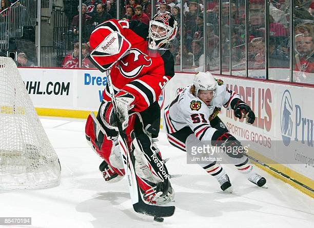 Goaltender Martin Brodeur of the New Jersey Devils clears the puck against Brian Campbell of the Chicago Blackhawks at the Prudential Center on March...