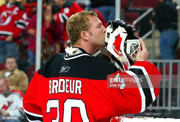 Goaltender Martin Brodeur of the New Jersey Devils kisses his mask for luck just prior to playing in his 1000th NHL regular season game against the...