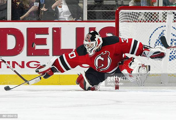 Goaltender Martin Brodeur of the New Jersey Devils knocks the puck away with his stick against the Carolina Hurricanes during Game Five of the...