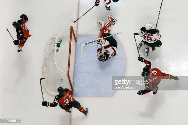 Goaltender Martin Brodeur of the New Jersey Devils looks back at the puck in the net as Stephen Weiss scores and Kris Versteeg and Tomas Fleischmann...