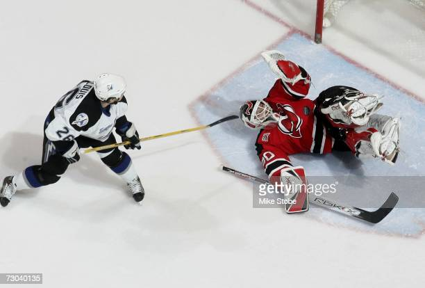 Goaltender Martin Brodeur of the New Jersey Devils makes a diving save during the shootout against Martin St. Louis of the Tampa Bay Lightning at the...