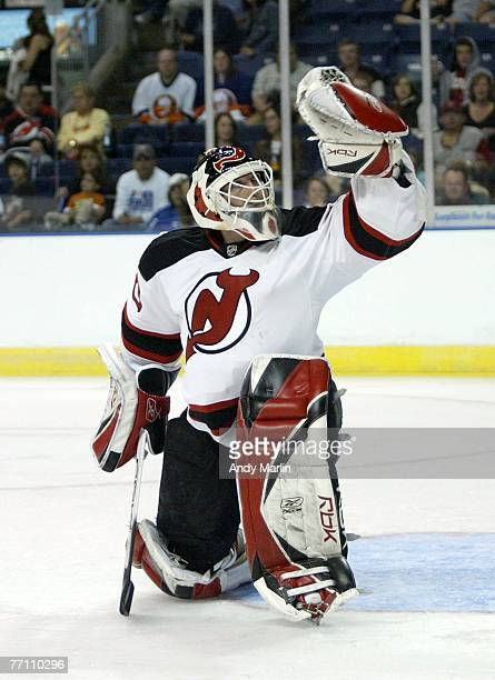 Goaltender Martin Brodeur of the New Jersey Devils makes a glove save against the New York Islanders during their preseason game at the Arena at...