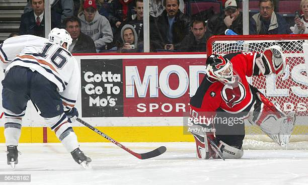Goaltender Martin Brodeur of the New Jersey Devils makes a save against center Jarret Stoll of the Edmonton Oilers during their game on December 13...