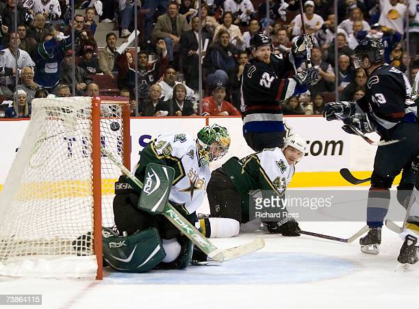 Goaltender Marty Turco and Philippe Boucher of the Dallas Stars sits dejected on the ice as Henrik Sedin and Daniel Sedin of the Vancouver Canucks...