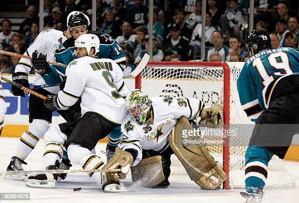 Goaltender Marty Turco of the Dallas Stars attempts to cover the puck as Mike Modano blocks out Jonathan Cheechoo of the San Jose Sharks during Game...