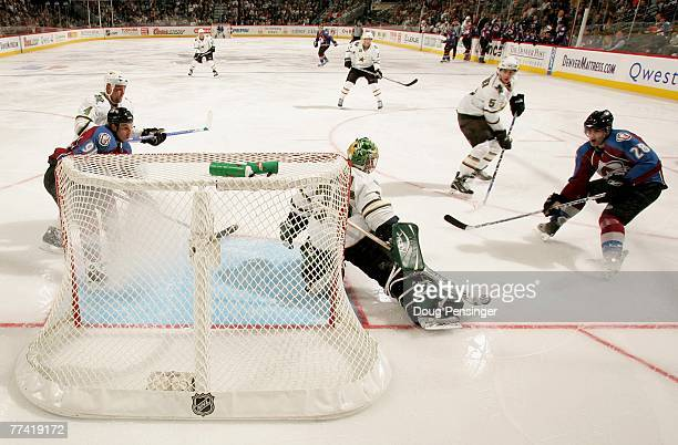 Goaltender Marty Turco of the Dallas Stars defends the goal against Ben Guite of the Colorado Avalanche during NHL action at the Pepsi Center on...