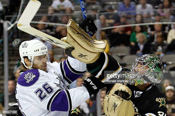 Goaltender Marty Turco of the Dallas Stars hits the puck down against Michal Handzus of the Los Angeles Kings at American Airlines Center on October...