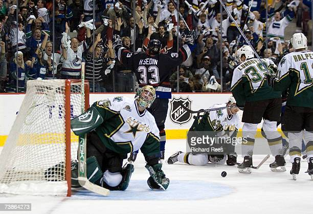 Goaltender Marty Turco of the Dallas Stars sits dejected on the ice as Henrik Sedin of the Vancouver Canucks celebrates his overtime winning goal...
