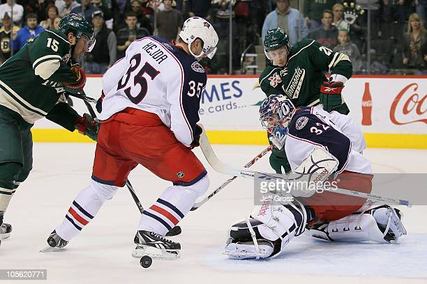 Goaltender Mathieu Garon of the Columbus Blue Jackets makes a kick save in front of teammate Jan Hejda and Andrew Brunette of the Minnesota Wild...