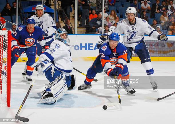 Goaltender Mathieu Garon of the Tampa Bay Lightning and teammate Brett Connolly defend the net against Josh Bailey of the New York Islanders on...