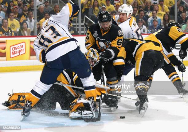 Goaltender Matt Murray of the Pittsburgh Penguins makes a save underneath Vernon Fiddler of the Nashville Predators as teammate Ron Hainsey looks on...