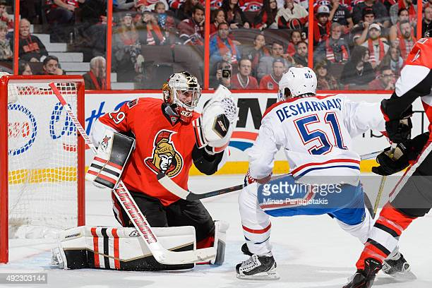 Goaltender Matt O'Connor of the Ottawa Senators gloves the puck in front of David Desharnais of the Montreal Canadiens during the NHL game at...