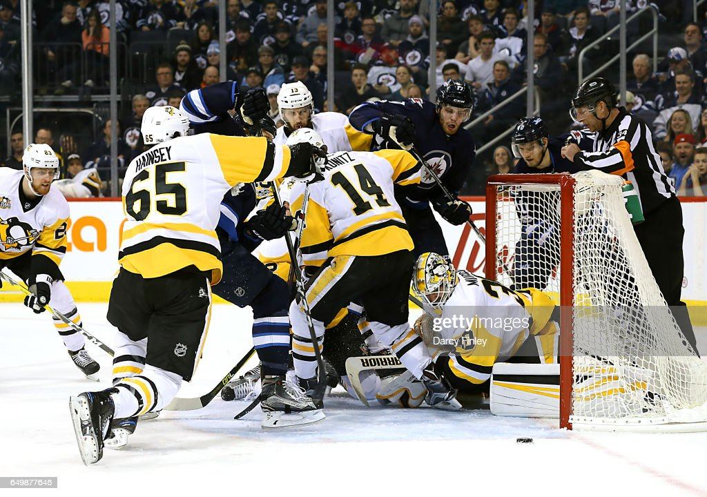 Goaltender Matthew Murray #30 of the Pittsburgh Penguins keeps his eye on the loose puck as Winnipeg Jets players crash the crease during third period action at the MTS Centre on March 8, 2017 in Winnipeg, Manitoba, Canada.
