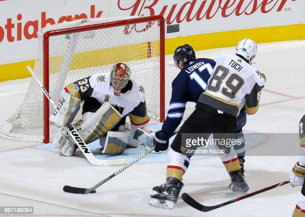 Goaltender Maxime Lagace of the Vegas Golden Knights guards the net as Adam Lowry of the Winnipeg Jets drives the puck towards the goal during third...