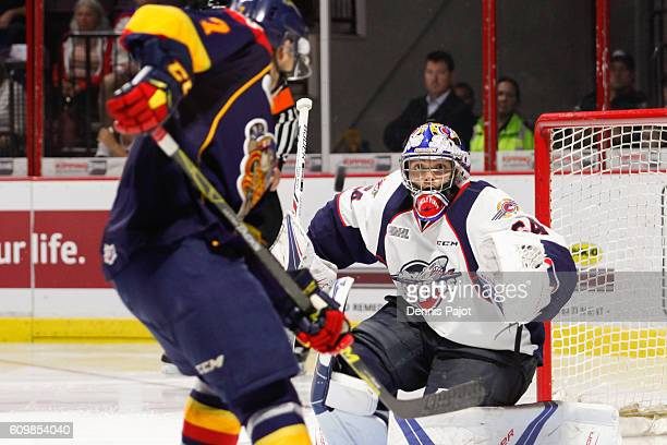 Goaltender Michael DiPietro of the Windsor Spitfires watches the puck on a rebound against forward Christian Girhiny of the Erie Otters on September...