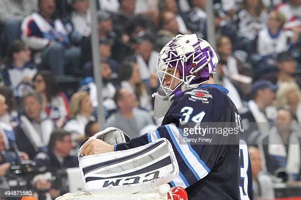 Goaltender Michael Hutchinson of the Winnipeg Jets adjusts his equipment during a third period stoppage in play against the Minnesota Wild at the MTS...