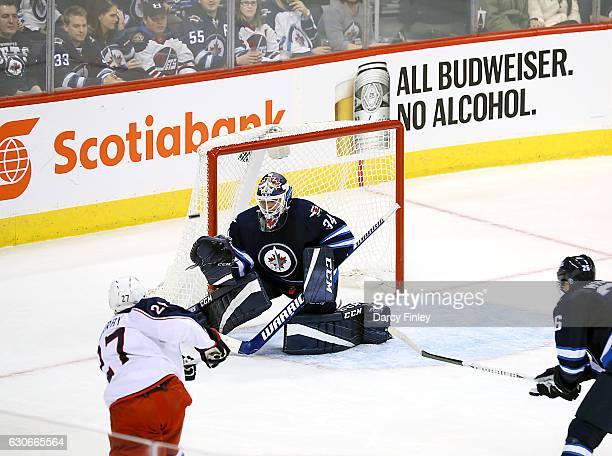 Goaltender Michael Hutchinson of the Winnipeg Jets guards the net as Ryan Murray of the Columbus Blue Jackets takes a shot on goal during second...