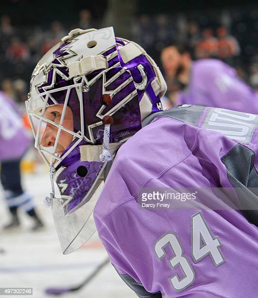 Goaltender Michael Hutchinson of the Winnipeg Jets looks on as he takes part in the pregame warm up sporting a lavender jersey and a specially...