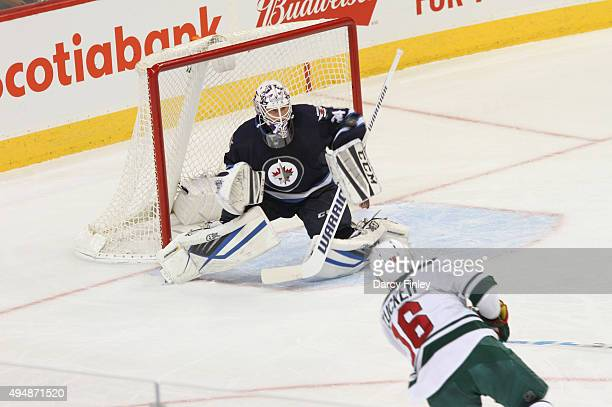 Goaltender Michael Hutchinson of the Winnipeg Jets makes a blocker save on a shot by Jason Zucker of the Minnesota Wild during second period action...