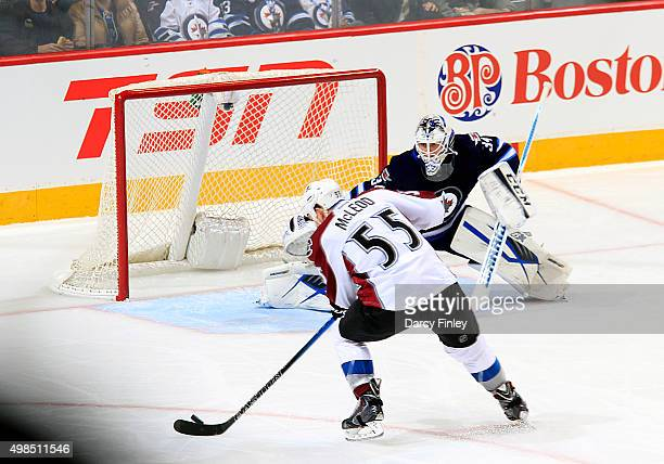 Goaltender Michael Hutchinson of the Winnipeg Jets slides across the crease as Cody McLeod of the Colorado Avalanche gets set to take a shot during...