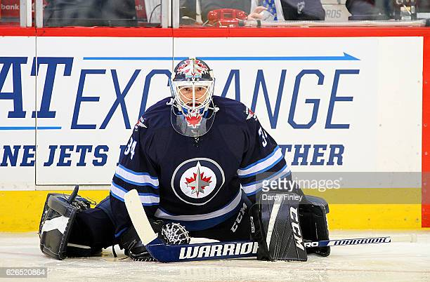 Goaltender Michael Hutchinson of the Winnipeg Jets stretches during the pregame warm up prior to NHL action against the New Jersey Devils at the MTS...