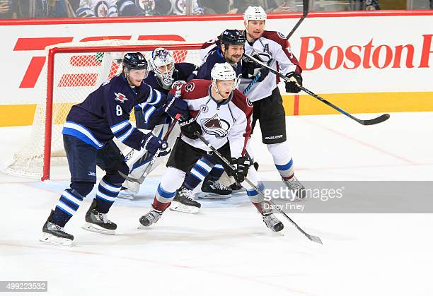 Goaltender Michael Hutchinson of the Winnipeg Jets tries to look past the screens set by teammates Jacob Trouba and Mark Stuart as they battle Carl...