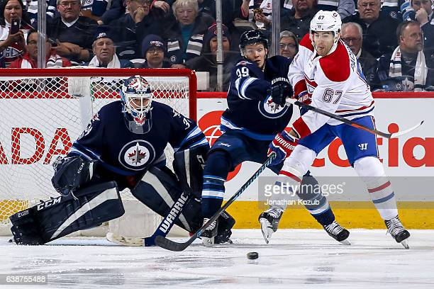 Goaltender Michael Hutchinson of the Winnipeg Jets watches as teammate Toby Enstrom battles Max Pacioretty of the Montreal Canadiens for the loose...