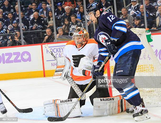 Goaltender Michal Neuvirth of the Philadelphia Flyers and Drew Stafford of the Winnipeg Jets keep an eye on the play during thirdperiod action at the...