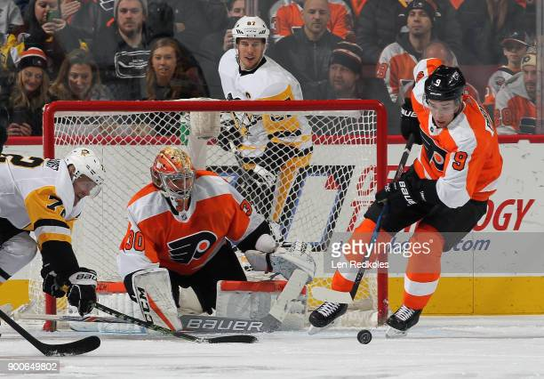 Goaltender Michal Neuvirth of the Philadelphia Flyers watches as Ivan Provorov skates the puck away from the reach of Patric Hornqvist of the...