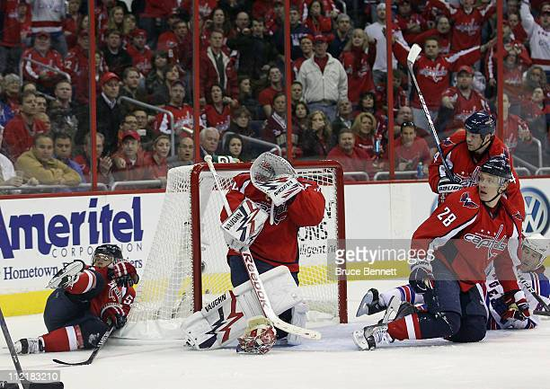 Goaltender Michal Neuvirth of the Washington Capitals covers up after losing his mask in his game against the New York Rangers in Game One of the...